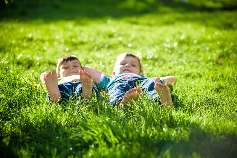 Children laying on grass. Family picnic in spring park stock image