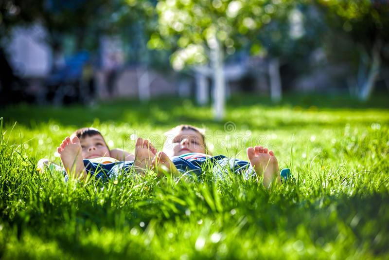 Children laying on grass. Family picnic in spring park. Image of several legs lying on the grass and resting. Relaxation happy childhood friendship concept royalty free stock images