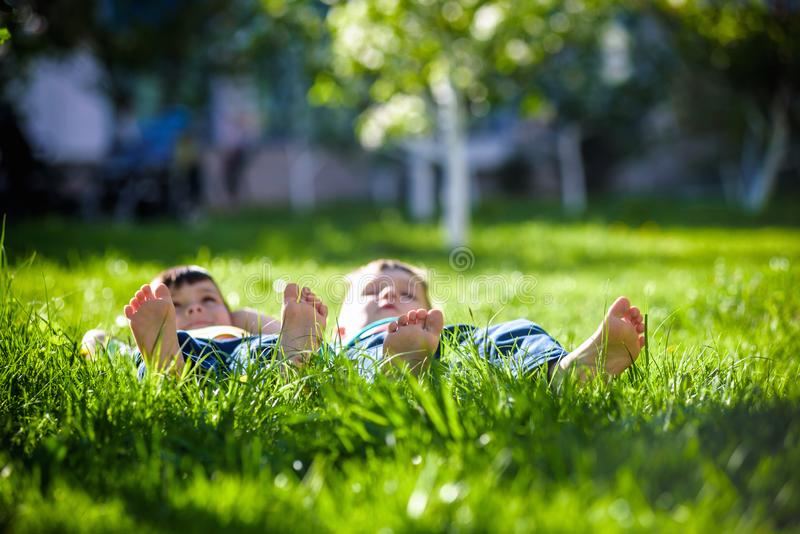 Children laying on grass. Family picnic in spring park royalty free stock photography