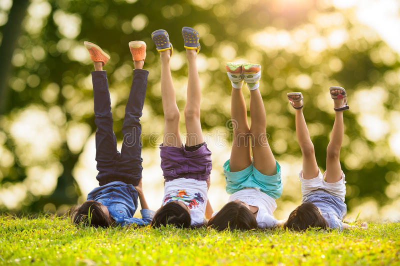 Children laying on grass. Group of happy children lying on green grass outdoors in spring park stock photo