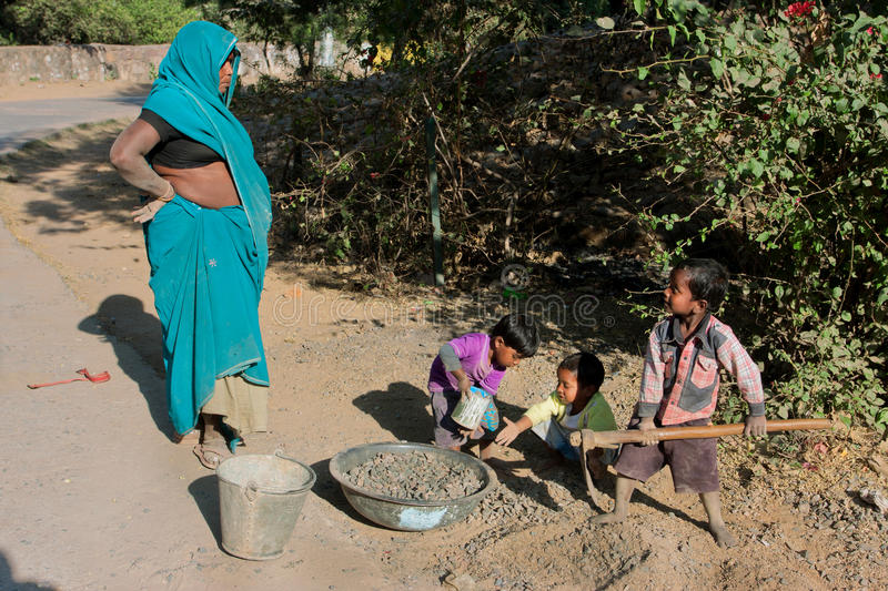 Children learn by mother how to repair roads stock image