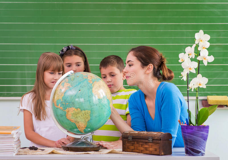 Children learn in school from the globe, Geography stock image