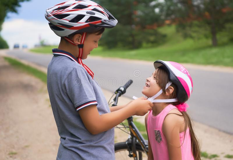 Children learn to ride bicycle in a park on summer day. Teenager boy helping preschooler girl to put on safety helmet stock images