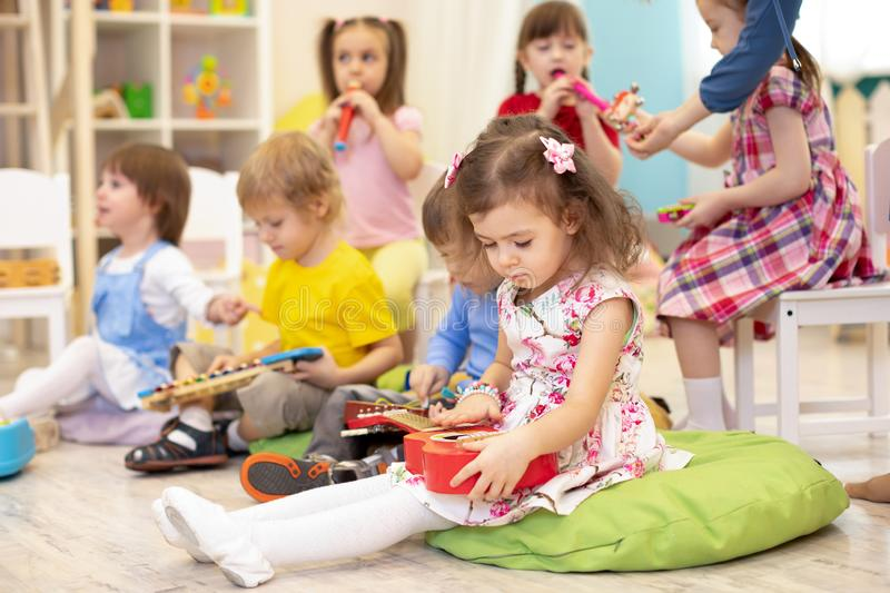 Children learning musical instruments on lesson in kindergarten royalty free stock photography