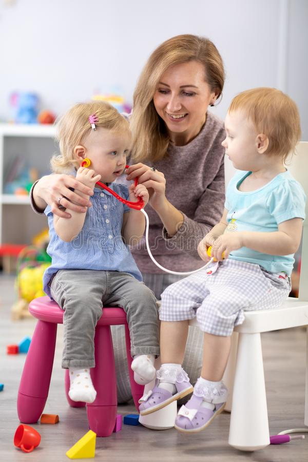 Children learning with a teacher are a doctor and patient. royalty free stock photo