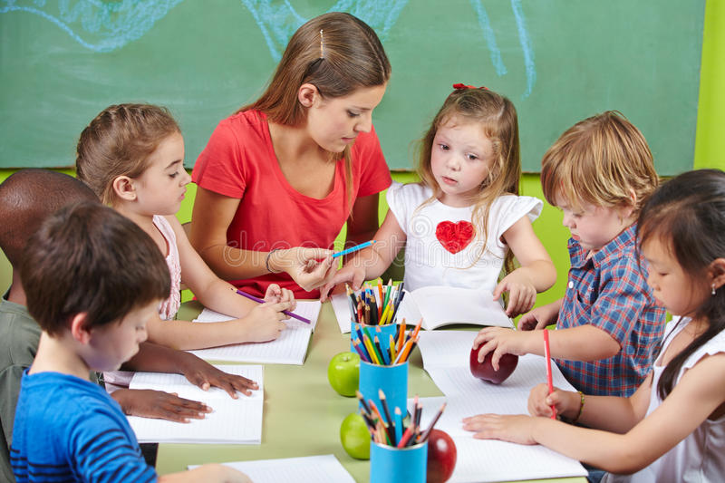 Children learning writing. Together in preschool with nursery teacher royalty free stock photo