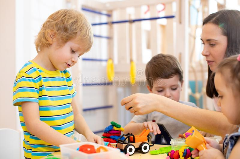 Children at lesson in kindergarten. Kids playing with plasticine with teacher in nursery playroom. stock images