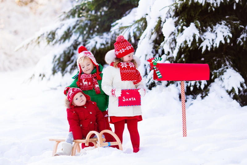 Children with letter to Santa at Christmas mail box in snow royalty free stock photography