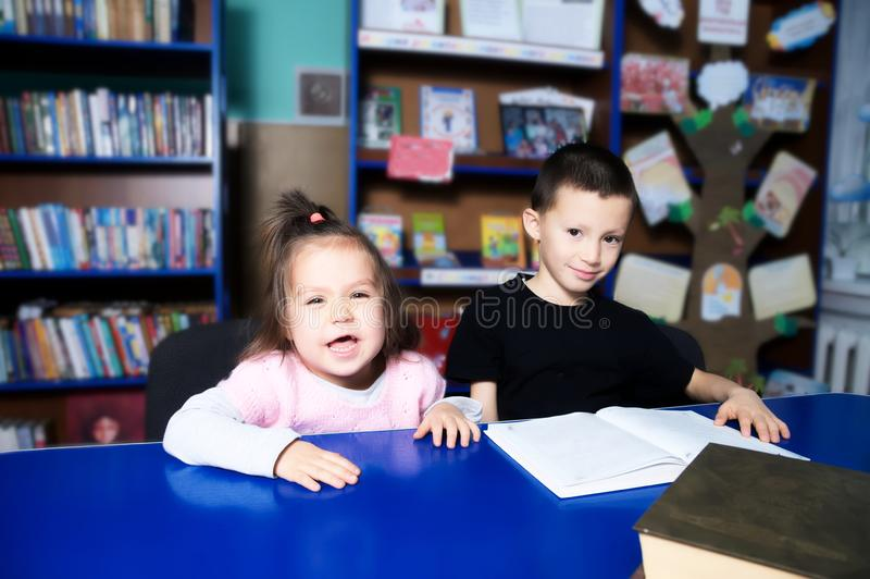 Children in library happy reading book. Little girl and boy learning stock image