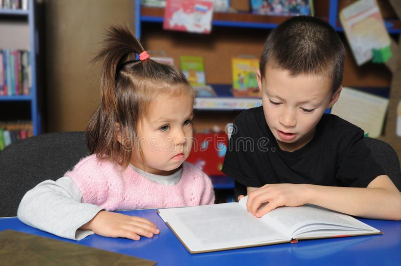 Children in library together learning. Little girl listening and boy reading book stock images