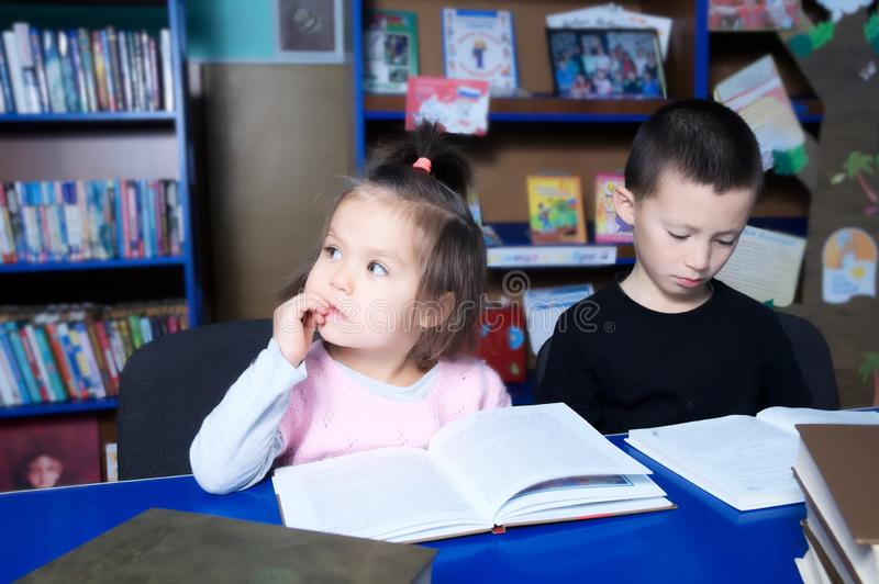 Children in library reading interesting book. Little girl and boy learning royalty free stock images