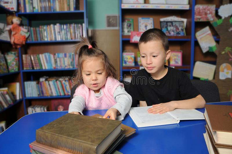 Children in library reading interesting book. Little girl and boy learning royalty free stock photos
