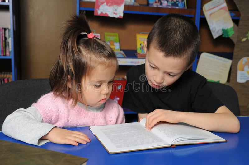 Children in library reading interesting book. Little girl and boy learning royalty free stock photo