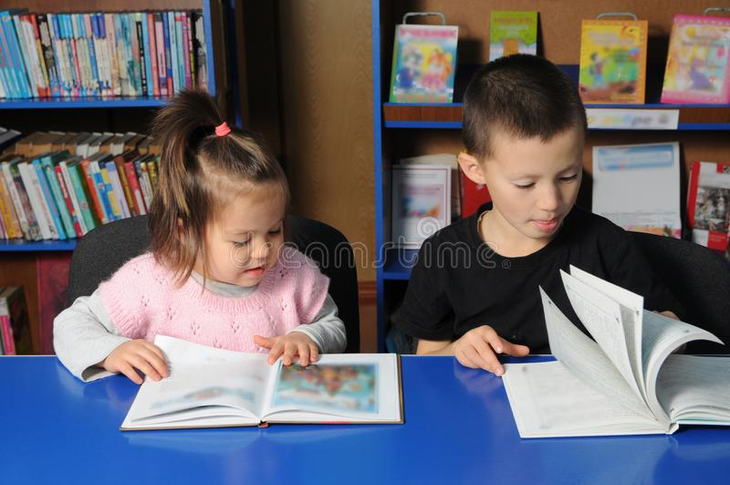 Children in library reading interesting book. Little girl and boy learning stock photo