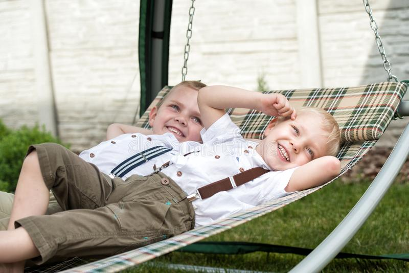 The two brothers are resting and having fun .Children lie in a hammock. royalty free stock images