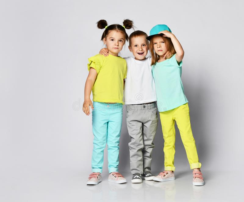 Children on a light background:  shot of three children in bright clothes, two girls and one boy. Triplets, brother and sisters. Studio portrait of children on royalty free stock images