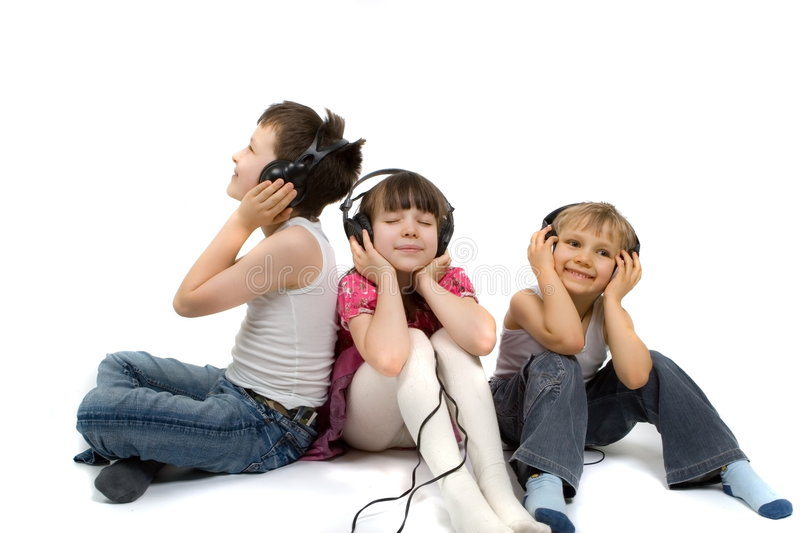 Children Listening To Music. Young girl and her two brothers sitting together, listening to music on headphones. Taken in studio; isolated on white background royalty free stock images