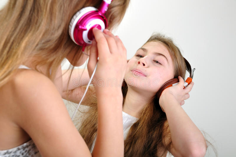 Children listening to music. Two young grils with headphones listening to music stock photo