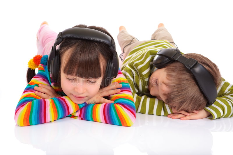 Children listening to music. Young girl and boy laying on their stomachs with their eyes closed, listening to music on headphones. Isolated against a white royalty free stock image