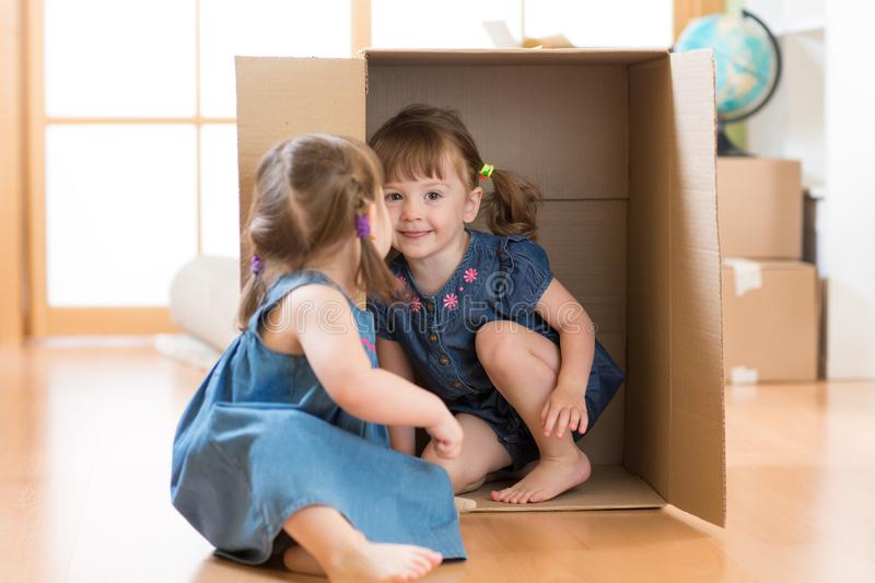 Children little girls playing inside box royalty free stock photos