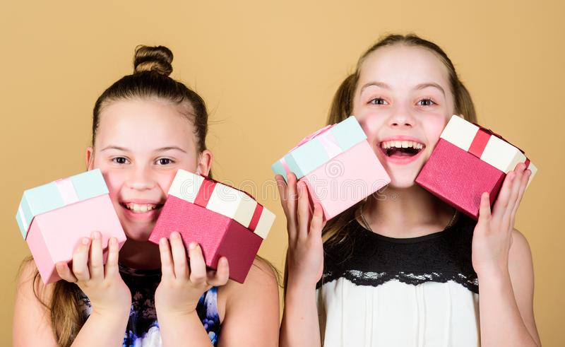 Children. Little sisters with gift. Surprise. Family sisterhood congratulation. Happy birthday. Holiday celebration. Boxing day. Christmas shopping. Small royalty free stock photos