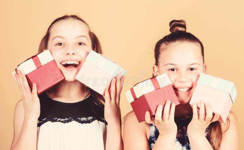 Children. Little sisters with gift. Surprise. Family sisterhood congratulation. Happy birthday. Holiday celebration. Boxing day. Christmas shopping. Small royalty free stock image