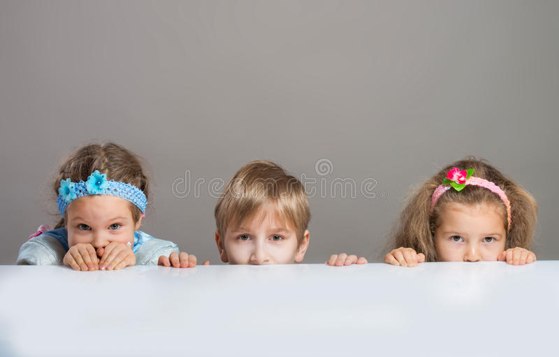 Children looking at camera from behind the table stock photo
