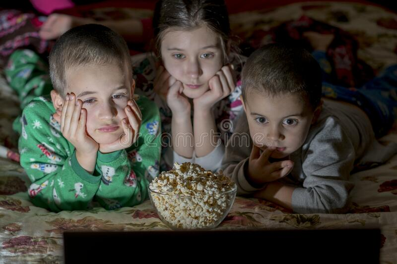 Children looking at laptop with cartoons showing before sleeping in bed. Three kids in bed watching a movie on a laptop and eating. Popcorn stock photos