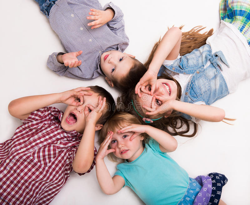 Children lying on the floor with hands imitating glasses stock photography