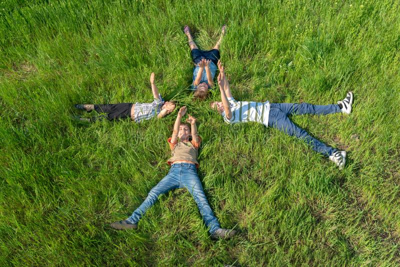 Children lying on the grass, happy and joyful brothers and sisters, top view stock images