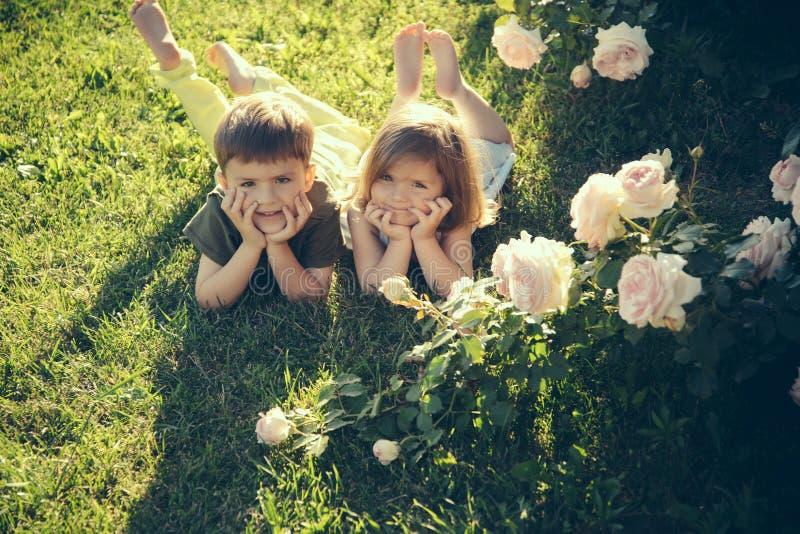 Children lying on green grass in summer garden royalty free stock photo