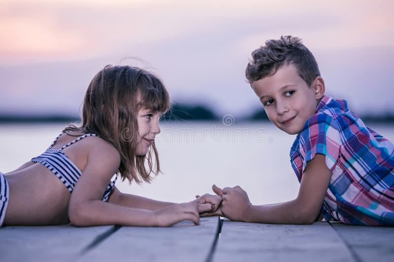 Children lying by the river and holding hands royalty free stock image