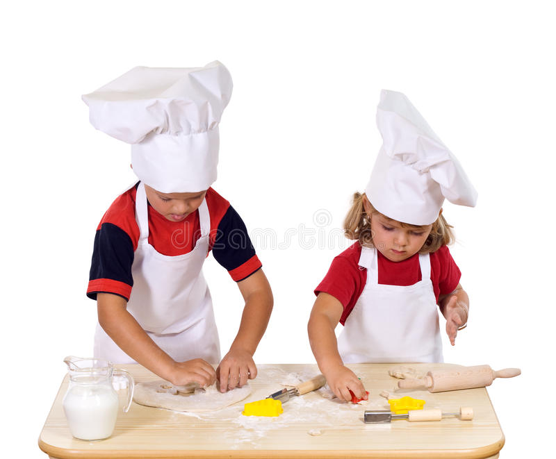 Children making cookies dressed as chefs. Children making christmas cookies dressed as chefs - cutting the dough to star and pine tree shapes stock images