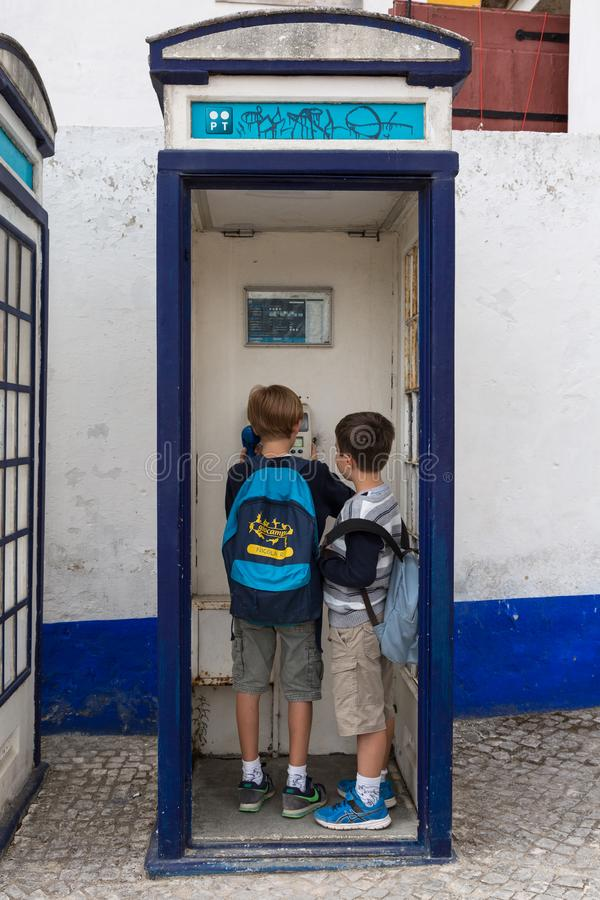 Children Making Phone Call inside Vintage Blue Phone Call Box in Portugal royalty free stock images