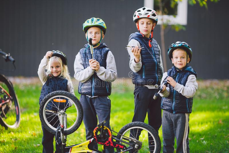 Children mechanics, bicycle repair. Happy kids fixing bike together outdoors in sunny day. Bicycle repair concept. Teamwork family royalty free stock photography