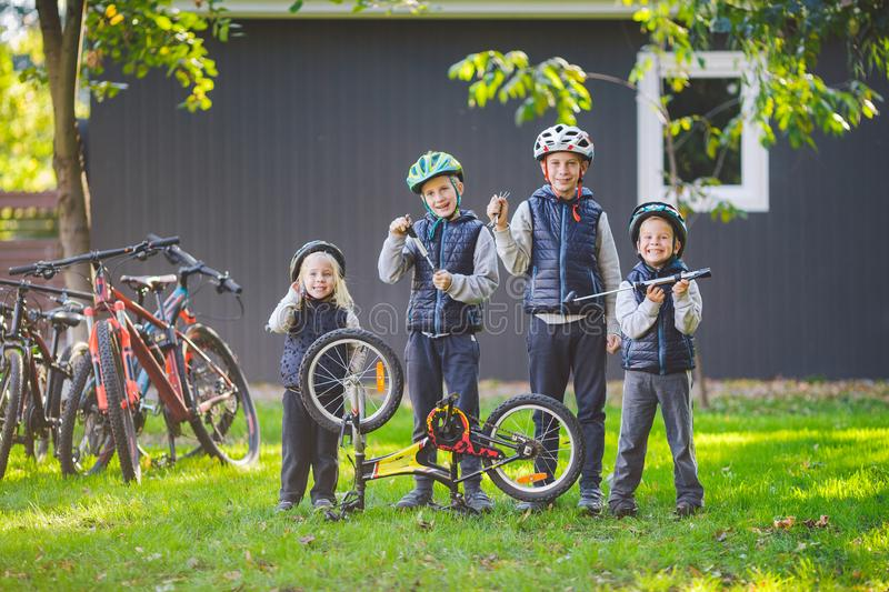 Children mechanics, bicycle repair. Happy kids fixing bike together outdoors in sunny day. Bicycle repair concept. Teamwork family. Posing with tools for royalty free stock photos