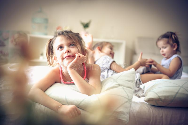 Children memories. Kids in bed. Three little girls in bed. Focus is on little girl. Space for copy stock photo