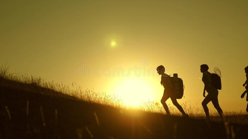 Children and mom with backpacks travel climb mountain in the sun. mom and daughters go camping. Family of tourists with royalty free stock photos