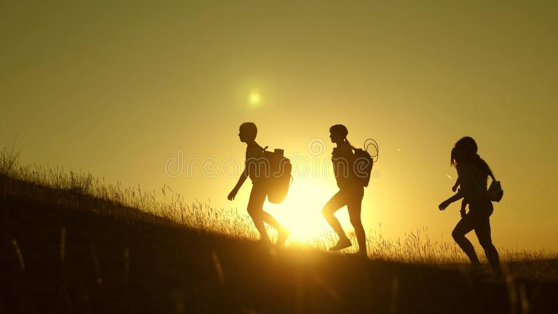 Children and mom with backpacks travel climb mountain in the sun. mom and daughters go camping. Family of tourists with stock photography