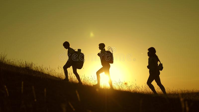 Children and mom with backpacks travel climb mountain in the sun. mom and daughters go camping. Family of tourists with royalty free stock image