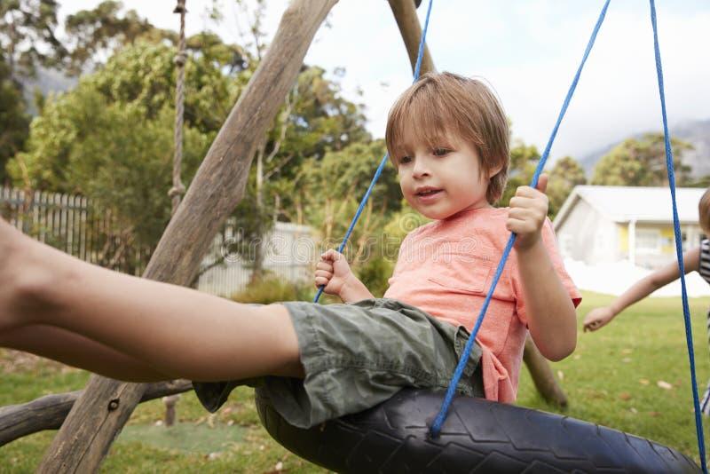 Children At Montessori School Playing On Swings During Break stock image