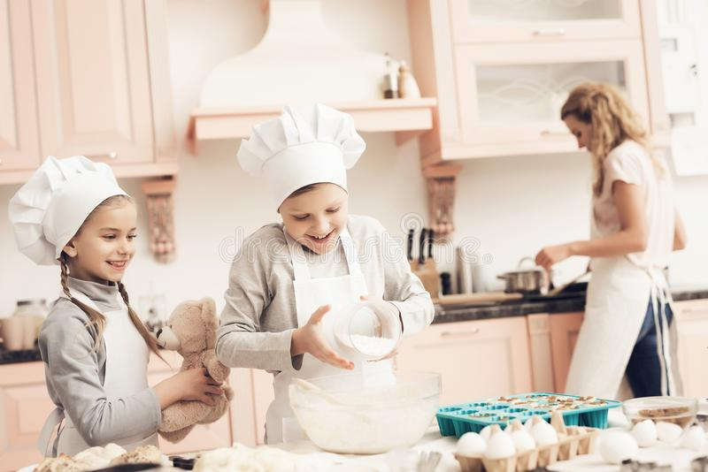 Children with mother in kitchen. Brother and sister are adding flour to dough. Children in chef`s hats with mother in kitchen. Brother and sister are adding royalty free stock images