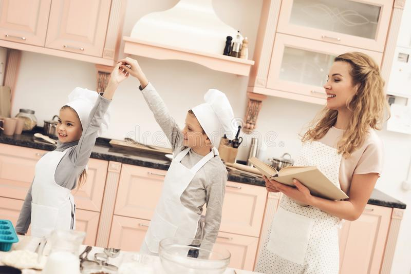 Children with mother in kitchen. Brother and sister are dancing, mother is holding cookbook. Children in chef`s hats with mother in kitchen. Brother and sister royalty free stock photo