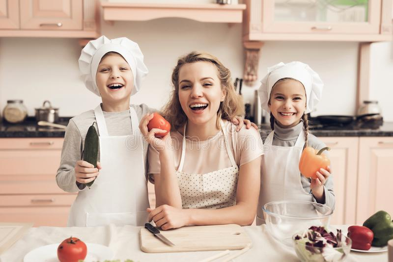 Children with mother in kitchen. Family is holding vegetables for salad. Children in chef`s hats with mother in kitchen. Family is holding vegetables for salad stock image