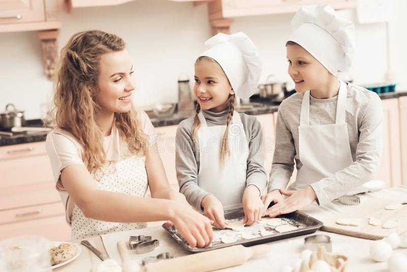 Children with mother in kitchen. Family is making cookies out of dough. Children in chef`s hats with mother in kitchen. Family is making cookies out of dough royalty free stock photos