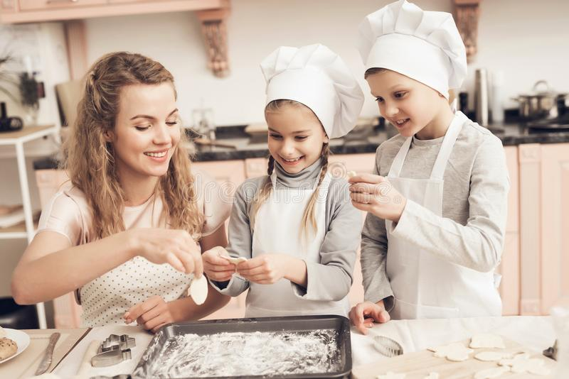 Children with mother in kitchen. Family is making cookies out of dough. Children in chef`s hats with mother in kitchen. Family is making cookies out of dough royalty free stock photography