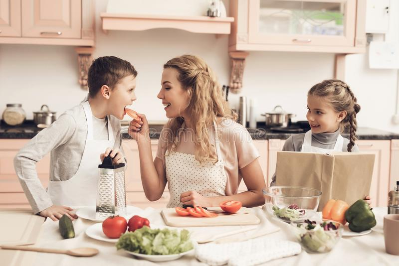 Children with mother in kitchen. Family is preparing vegetables for salad. Children with mother at kitchen table in kitchen. Family is preparing vegetables for royalty free stock images