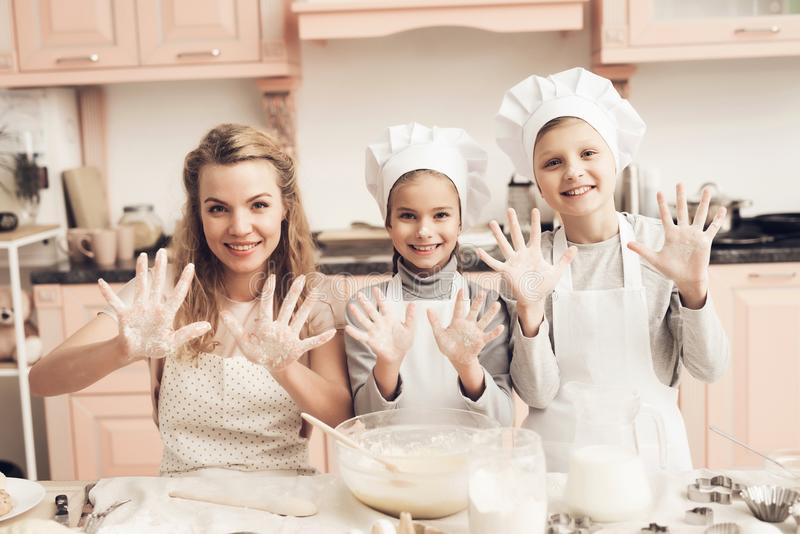 Children with mother in kitchen. Family is showing on camera hands in flour. Children in chef`s hats with mother in kitchen. Family is showing on camera hands royalty free stock photo