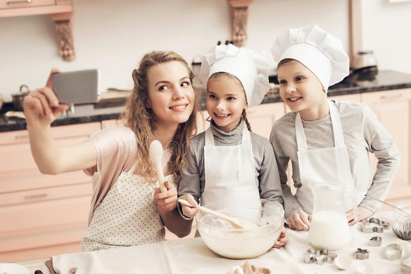 Children with mother in kitchen. Family is taking selfie on phone. Children in chef`s hats with mother in kitchen. Family is taking selfie on phone stock photography