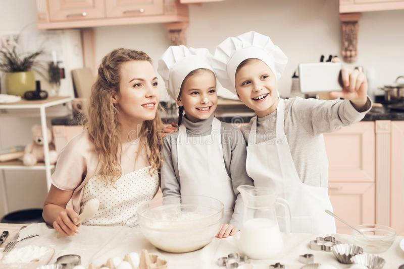 Children with mother in kitchen. Family is taking selfie on phone. Children in chef`s hats with mother in kitchen. Family is taking selfie on phone stock photo